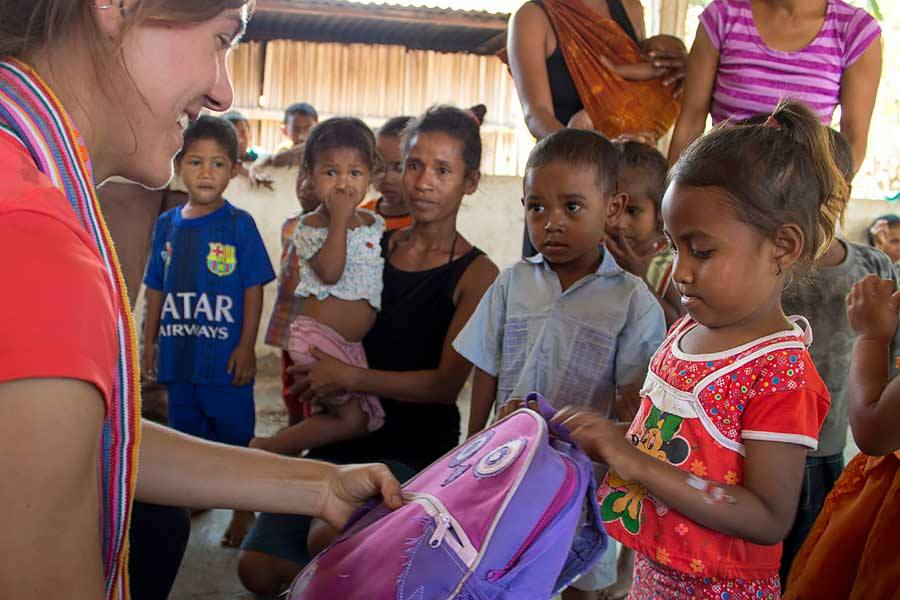 Eliza handing out schoolbags and toothbrushes